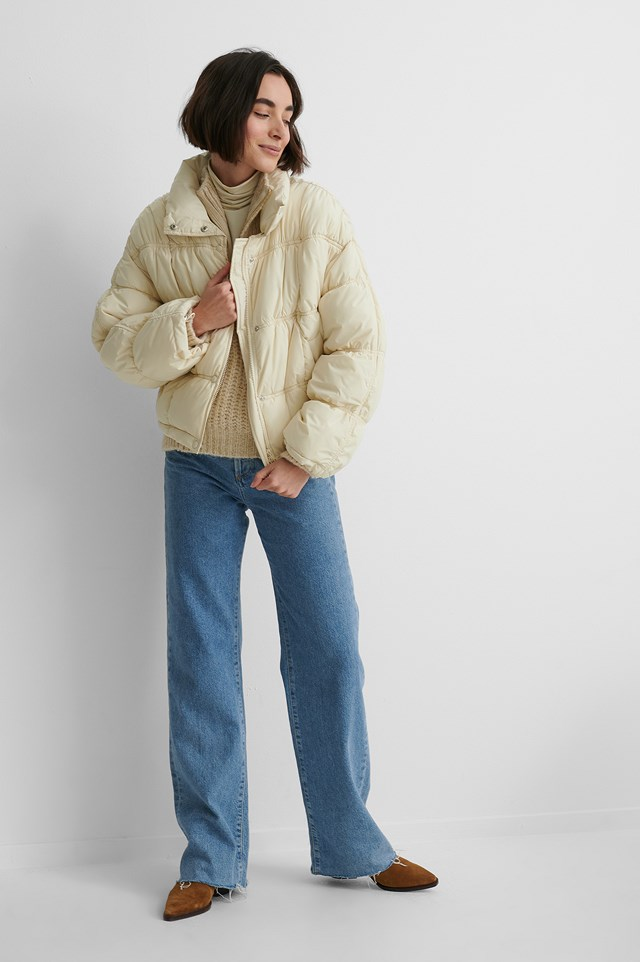 Shirred Detail Padded Jacket with Wide Denim a Knitted Sweater and Brown Boots.