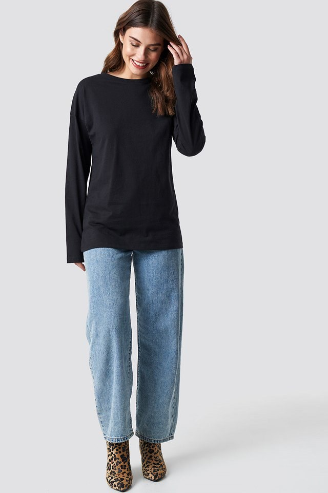 Unisex Black Long-Sleeve Top with Wide Denim Jeans and Leo Printed Boots.